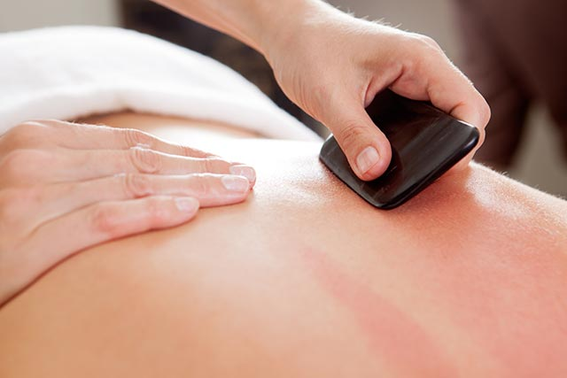 Image: Chronic lower back pain can be reduced with Gua Sha therapy