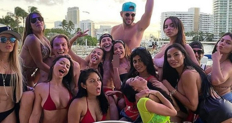 Image: Doctor who demanded mandatory mask law pictured partying maskless on boat surrounded by bikini-clad women